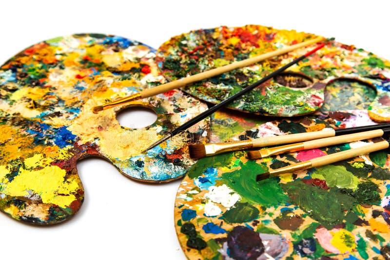 Paleta con las pinturas coloridas Paleta colorida de la pintura al óleo con un cepillo que alcanza adentro Tulipán en un fondo bl imágenes de archivo libres de regalías
