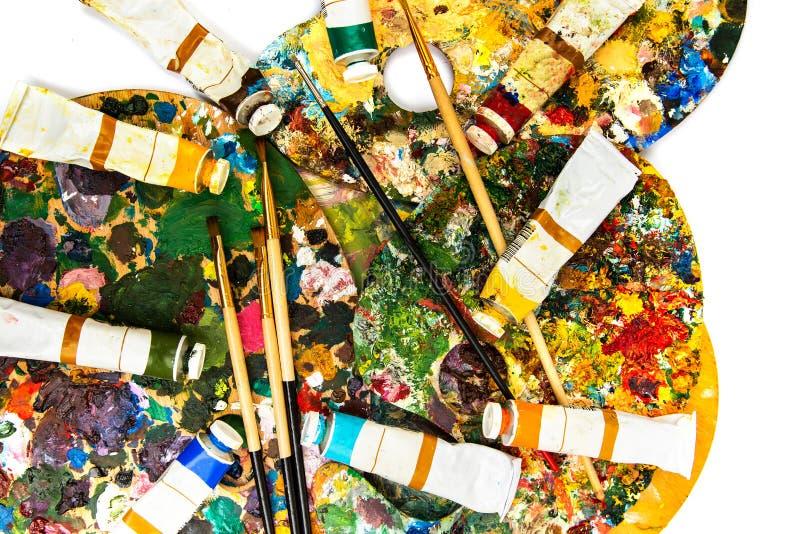 Paleta con las pinturas coloridas Paleta colorida de la pintura al óleo con un cepillo que alcanza adentro Tulipán en un fondo bl imagen de archivo libre de regalías