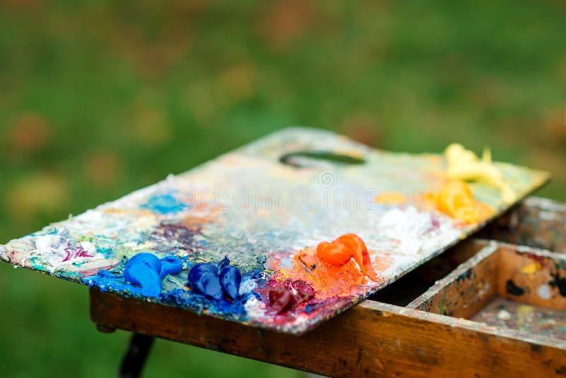 Paleta da arte no fundo blured natureza O artista pinta uma imagem de pinturas de ?leo Paleta suja da arte Cores acr?licas prelim foto de stock