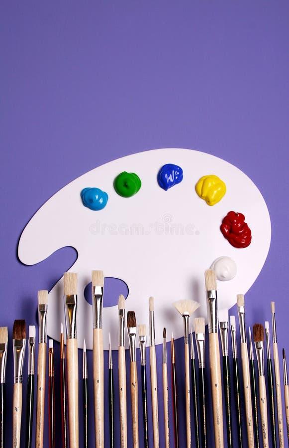 Paleta da pintura do artista com as pinturas e as escovas, simbólicas da arte fotos de stock