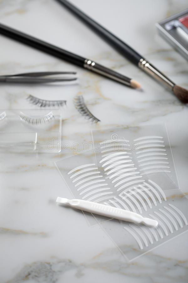 Paleta da sombra para os olhos, escovas, chicotes falsificados, pinça e fitas dobro do vinco artificial da pálpebra para a compos fotos de stock royalty free