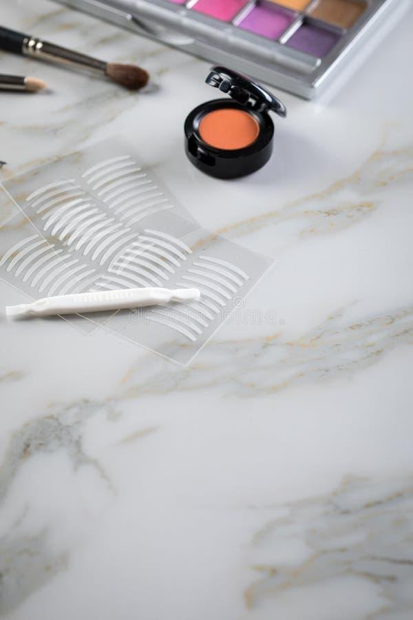 Paleta da sombra para os olhos, escovas, chicotes falsificados, pin?a e fitas dobro do vinco artificial da p?lpebra para a compos imagens de stock