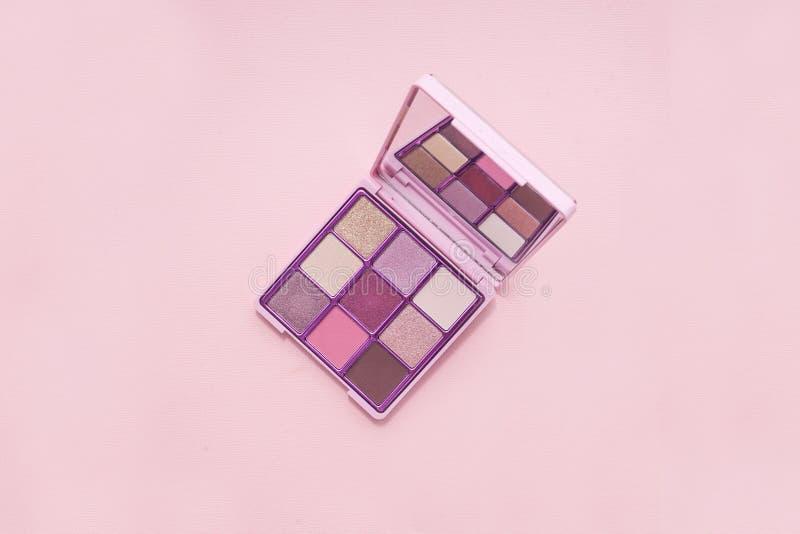 A paleta da vista superior do cosm?tico cor-de-rosa comp?e com um espelho no fundo cor-de-rosa, minimalismo colorido das sombras, fotografia de stock