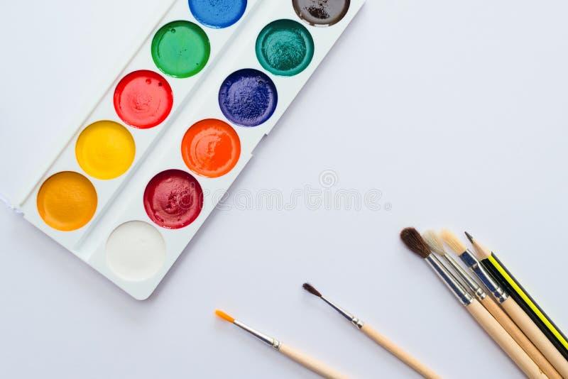 Paleta das aquarelas e dos pincéis no fundo do Livro Branco Acessórios para tirar Tema da arte e da educação imagens de stock royalty free