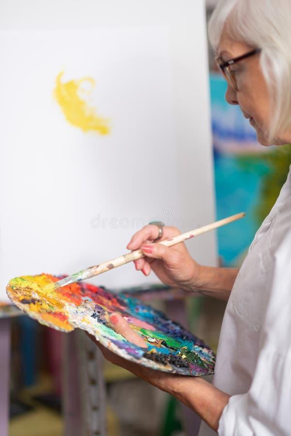 Paleta de colores y pintura envejecidas de la tenencia de la mujer con aguazo fotos de archivo libres de regalías