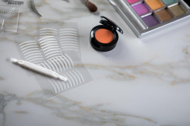 Paleta de la sombra de ojos, cepillos, latigazos falsos, pinzas y cintas dobles del pliegue artificial del párpado para el maquil fotografía de archivo libre de regalías