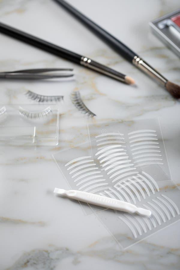 Paleta de la sombra de ojos, cepillos, latigazos falsos, pinzas y cintas dobles del pliegue artificial del párpado para el maquil fotos de archivo libres de regalías