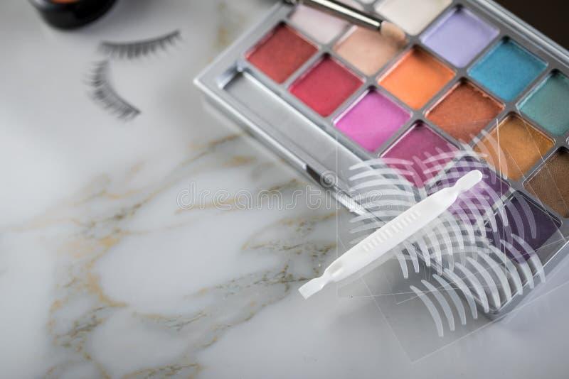Paleta de la sombra de ojos, cepillos, latigazos falsos, pinzas y cintas dobles del pliegue artificial del párpado para el maquil imagen de archivo