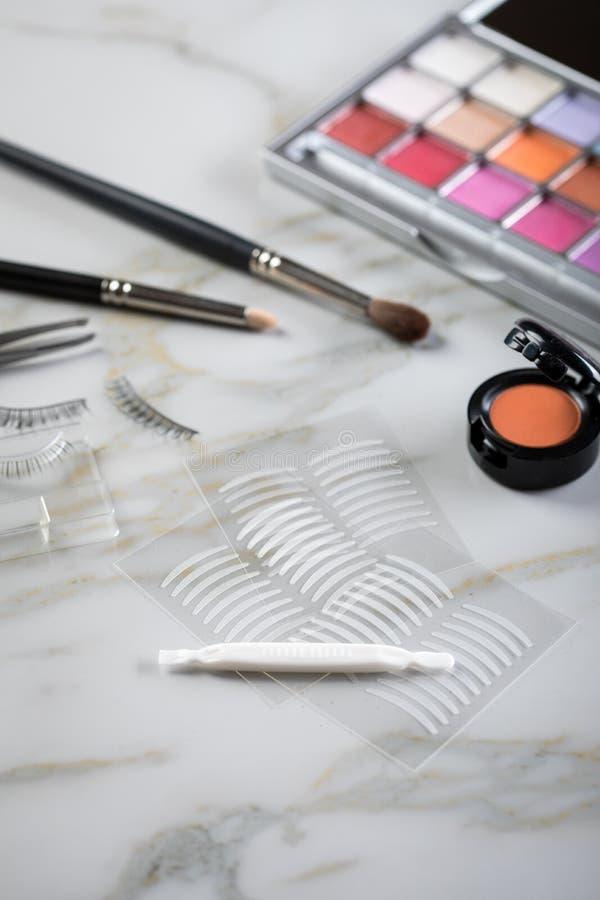 Paleta de la sombra de ojos, cepillos, latigazos falsos, pinzas y cintas dobles del pliegue artificial del párpado para el maquil foto de archivo libre de regalías