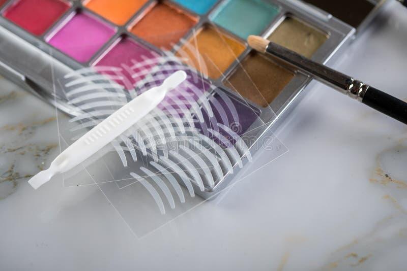 Paleta de la sombra de ojos, cepillos y cintas dobles del pliegue artificial del párpado para el maquillaje del ojo en belleza fotos de archivo