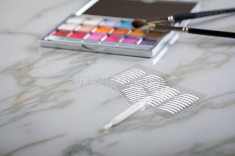 Paleta de la sombra de ojos, cepillos y cintas dobles del pliegue artificial del párpado para el maquillaje del ojo en la belleza fotos de archivo