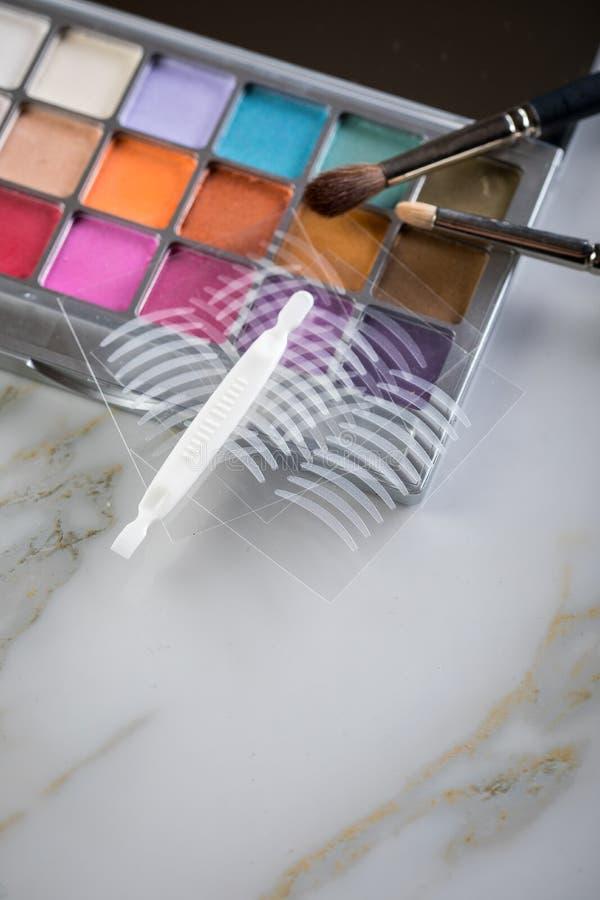 Paleta de la sombra de ojos, cepillos y cintas dobles del pliegue artificial del párpado para el maquillaje del ojo en la belleza foto de archivo libre de regalías