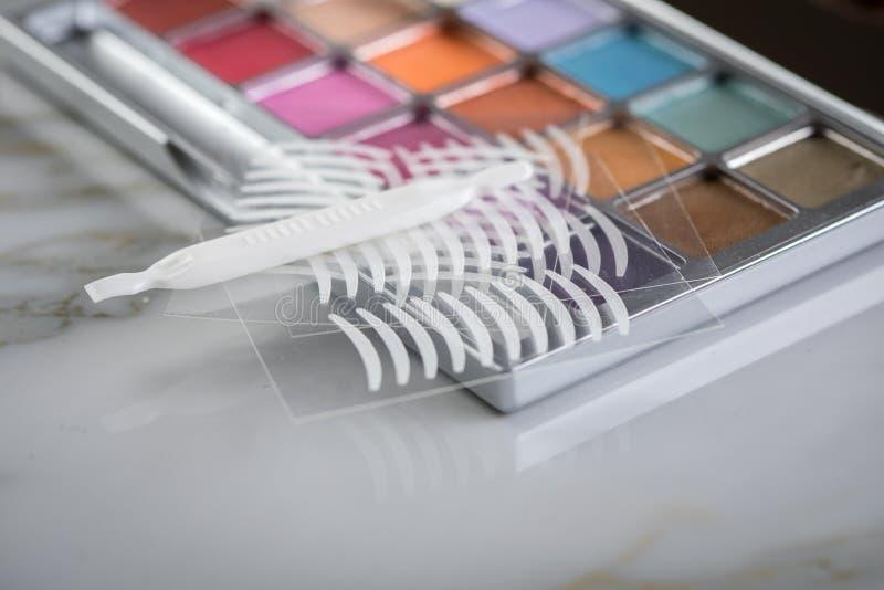Paleta de la sombra de ojos, cepillos y cintas dobles del pliegue artificial del párpado para el maquillaje del ojo en la belleza imágenes de archivo libres de regalías