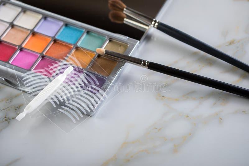 Paleta de la sombra de ojos, cepillos y cintas dobles del pliegue artificial del párpado para el maquillaje del ojo en la tabla d foto de archivo