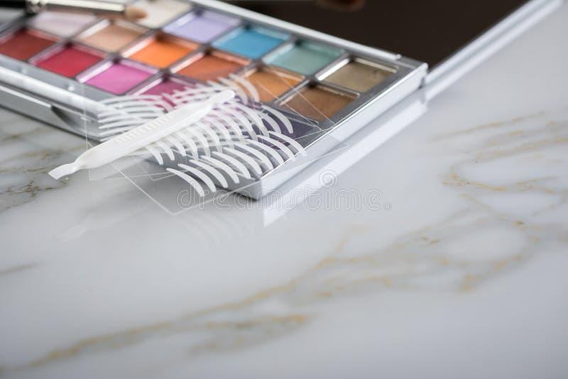 Paleta de la sombra de ojos, cepillos y cintas dobles del pliegue artificial del párpado para el maquillaje del ojo en la tabla d imagenes de archivo