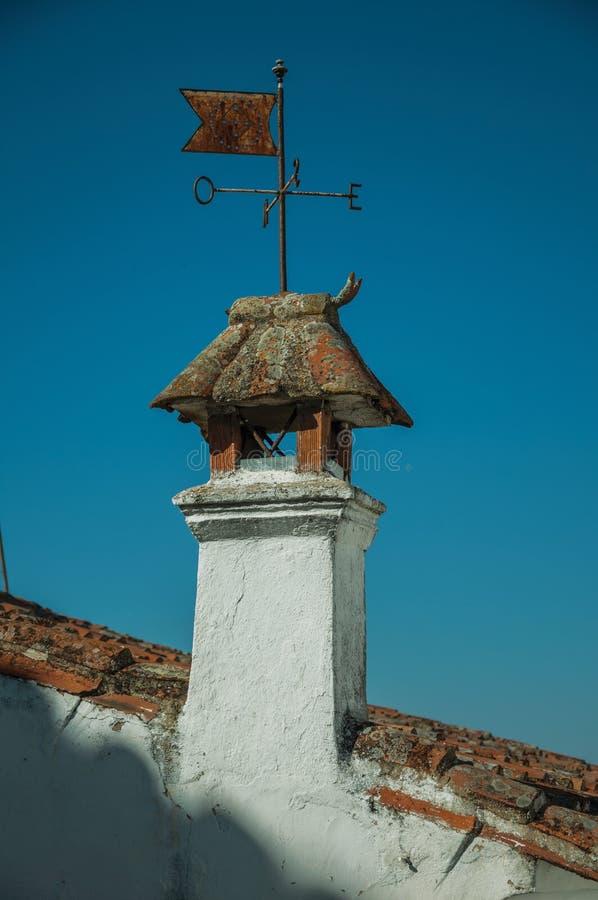 Paleta de viento del hierro sobre la chimenea en tejado imagenes de archivo