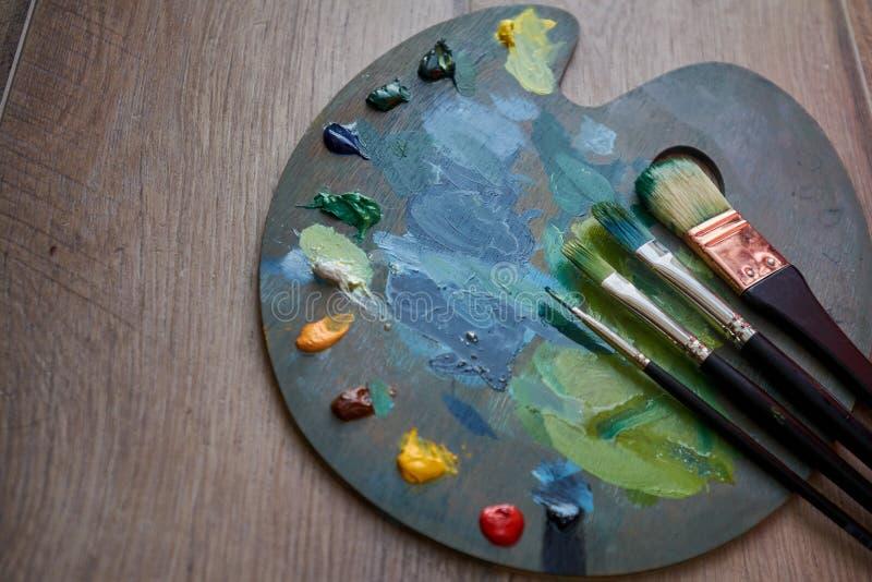 Paleta del artista con las pinturas y los cepillos de aceite en un fondo de madera imágenes de archivo libres de regalías