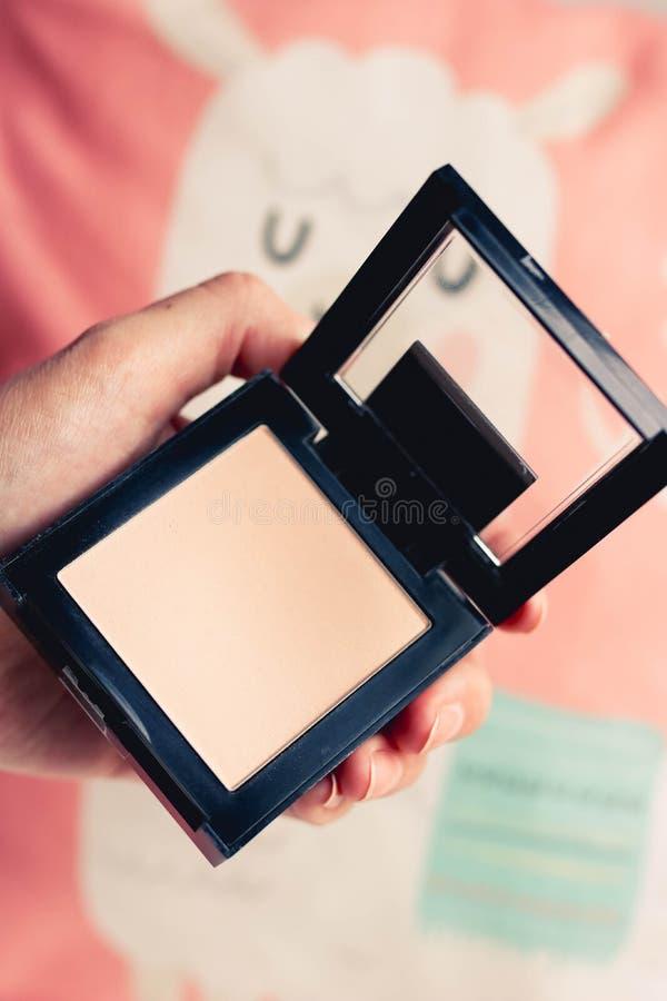 Paleta do pó preto da forma nas mãos fêmeas no fundo colorido Comp?e o conceito fotografia de stock royalty free