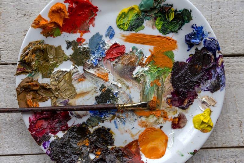 Paleta e escova da arte com lotes da pintura das cores, da pintura à têmpera e de óleo foto de stock royalty free