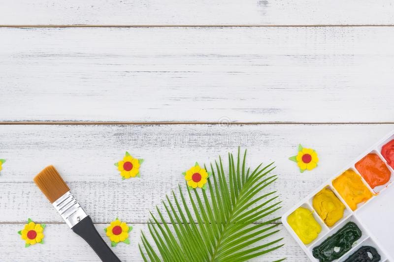 A paleta e o pincel da aquarela decoram com folhas da samambaia e as flores de papel amarelas imagem de stock
