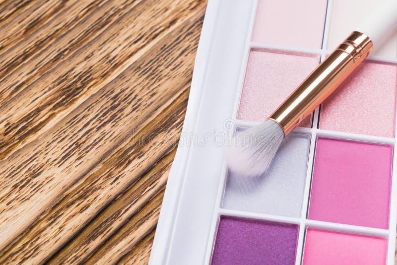 Paleta eyeshadow w menchiach barwi z szczotkarskim kłamstwem na drewnianym tle fotografia royalty free