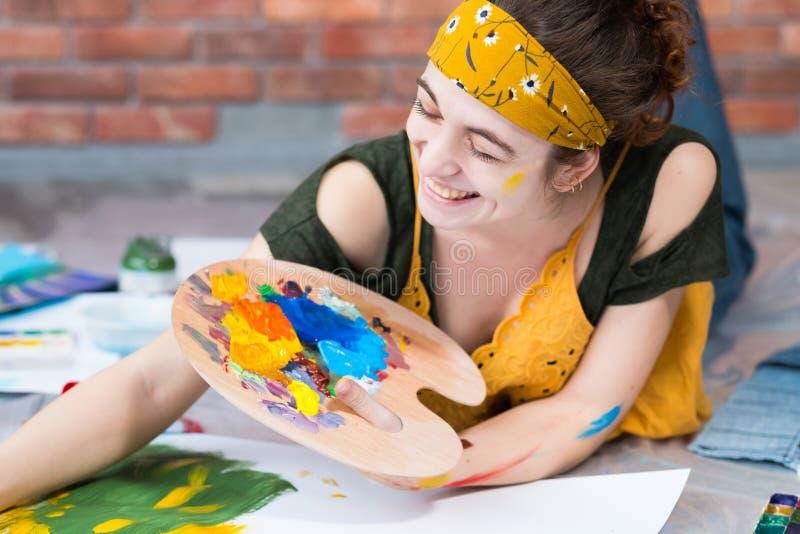 Paleta fêmea feliz do pintor do estúdio da arte da casa fotografia de stock