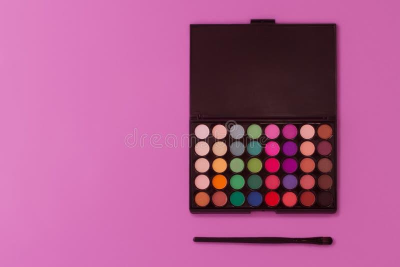 Paleta multicolora profesional de la sombra de ojos en un fondo purpúreo claro fotos de archivo