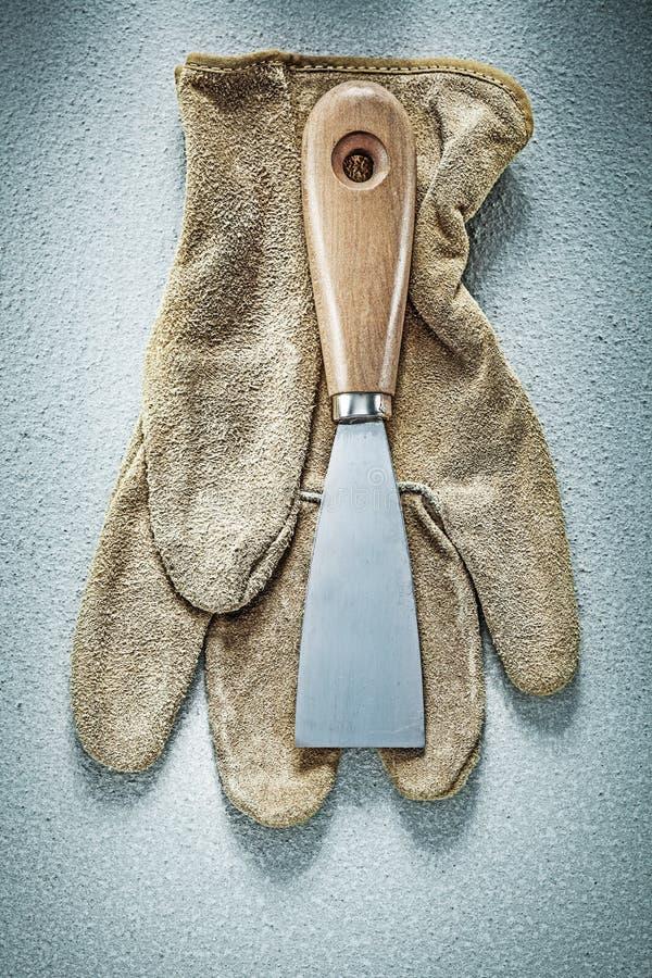 Paleta noża zbawcze rękawiczki na betonowej powierzchni budowie kantują obraz royalty free