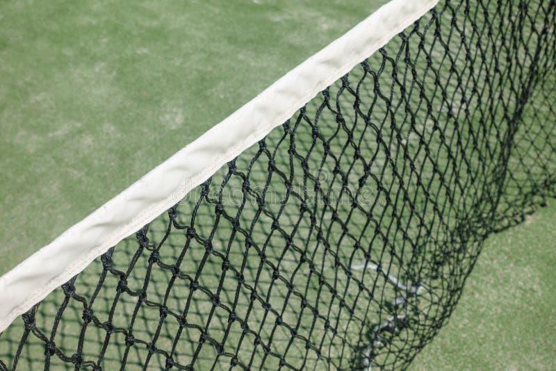 Paleta o red del tenis en la corte Tierra verde foto de archivo