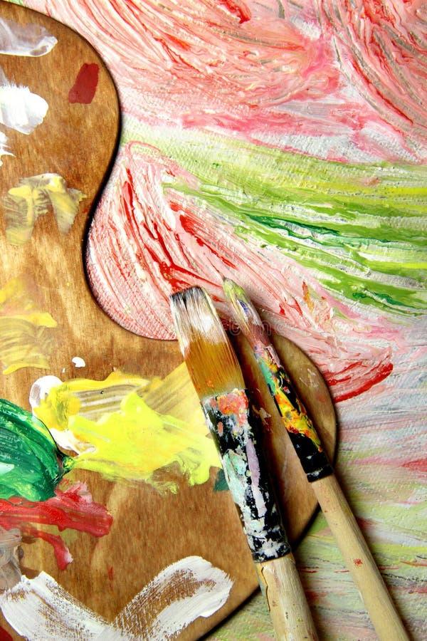 Paleta, pincéis e imagem da arte com flores imagem de stock