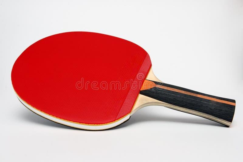 Paleta roja del ping-pong en un fondo blanco imagenes de archivo