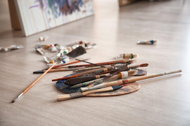 Paleta z narzędziami i farbami na podłodze w warsztacie fotografia royalty free