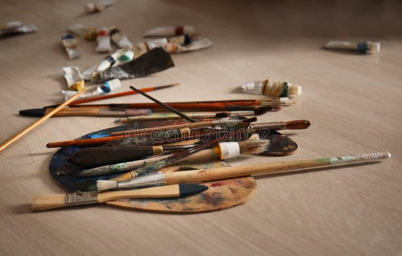 Paleta z narzędziami i farbami na podłodze w warsztacie obraz stock