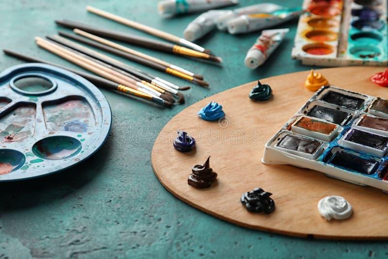 Paletas da pintura com as escovas na tabela foto de stock royalty free