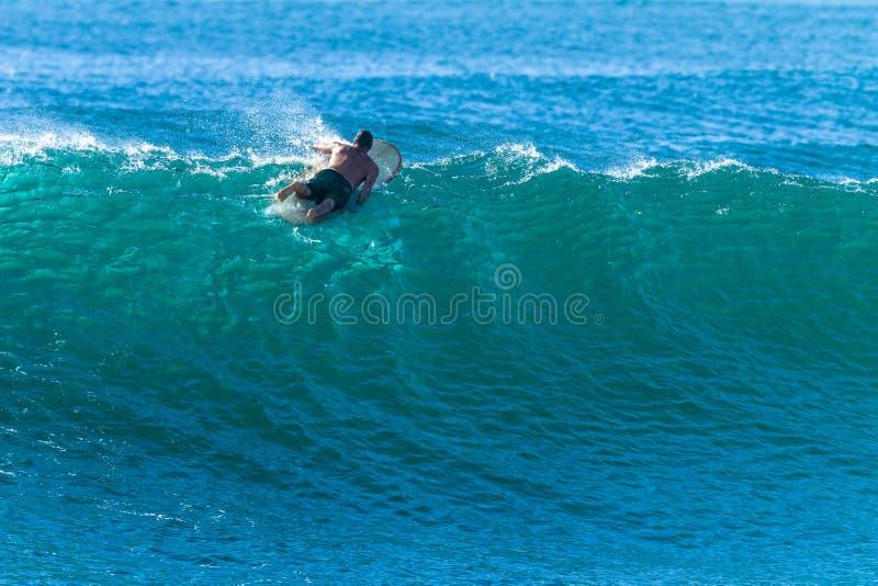 Paletas de la persona que practica surf sobre el golpeo Cresting del escape de la onda foto de archivo