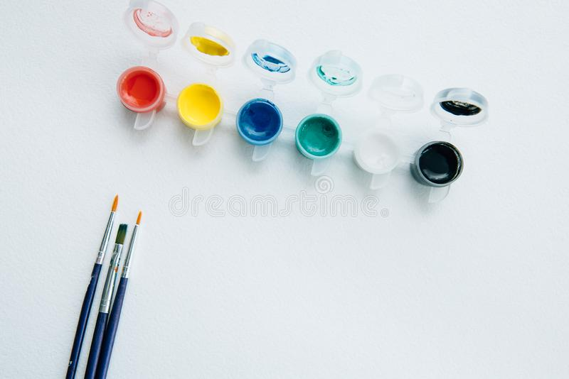 Palett av akrylmålarfärger och borstar på teckningspapper, bästa sikt Målning- och konsttema arkivfoto