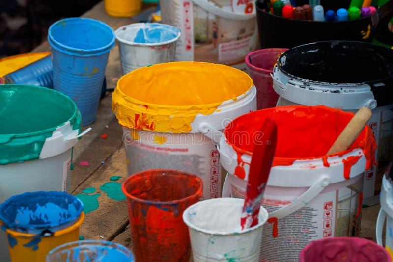 Palett för akrylmålarfärger, målade borstar på wood bakgrund som befläckas med olik färg Children& x27; s-kreativitet royaltyfri bild