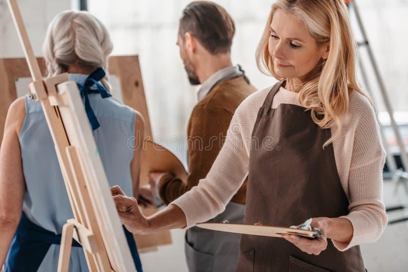 palett och målning för härlig mogen kvinna hållande på staffli under konstgrupp arkivbild