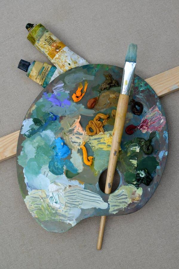 Palette avec des peintures et une brosse dans la perspective d'une toile photo stock