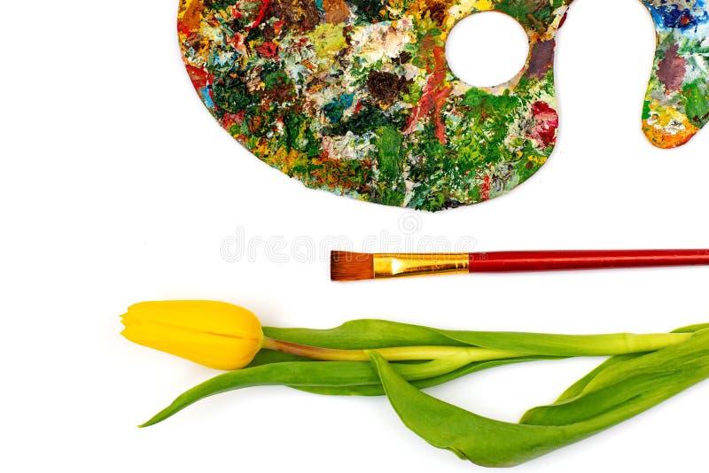 Palette avec les peintures colorées Palette colorée de peinture à l'huile avec une brosse atteignant dedans Tulipe sur un fond bl photographie stock