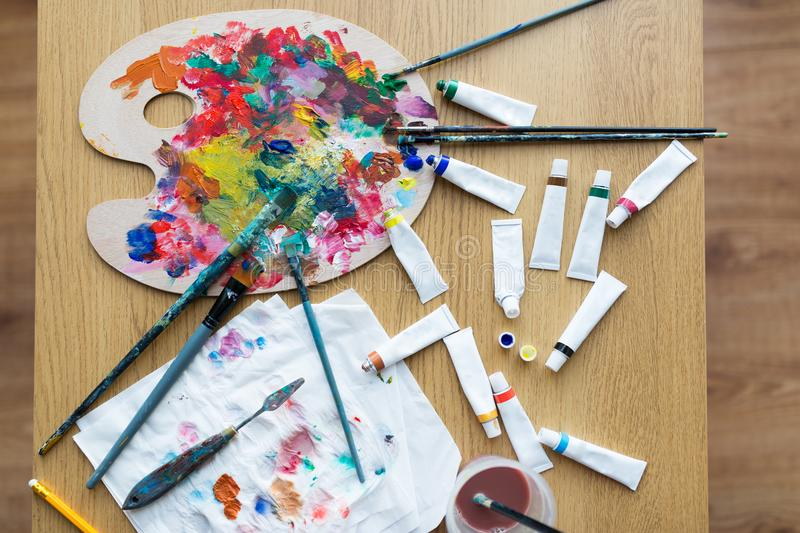 Palette, brushes and paint tubes on table. Fine art, creativity and artistic tools concept - palette, brushes and paint tubes on table royalty free stock photos