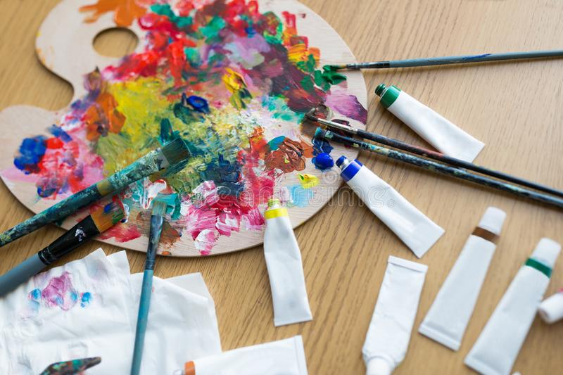 Palette, brushes and paint tubes on table. Fine art, creativity and artistic tools concept - close up of palette, brushes and paint tubes on table royalty free stock photos