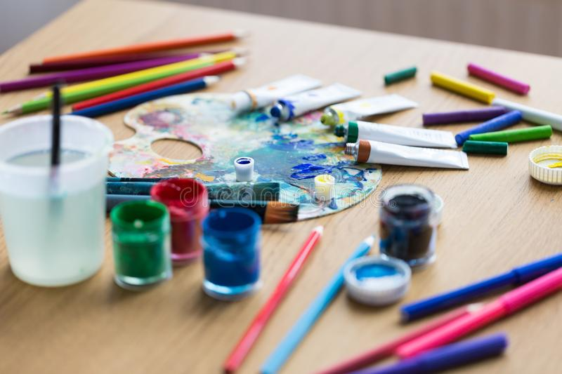 Palette, brushes and paint tubes on table. Fine art, creativity and artistic tools concept - palette, brushes, paint tubes and gouache colors on table stock image