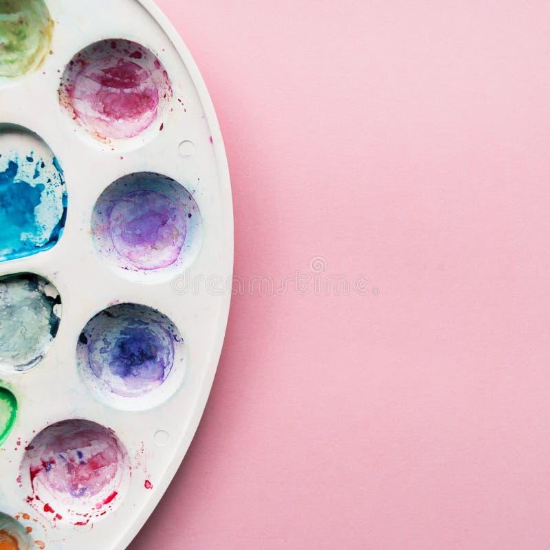 Palette d'aquarelle sur un pâle - fond en pastel rose Endroit pour votre conception, texte, etc. photos stock