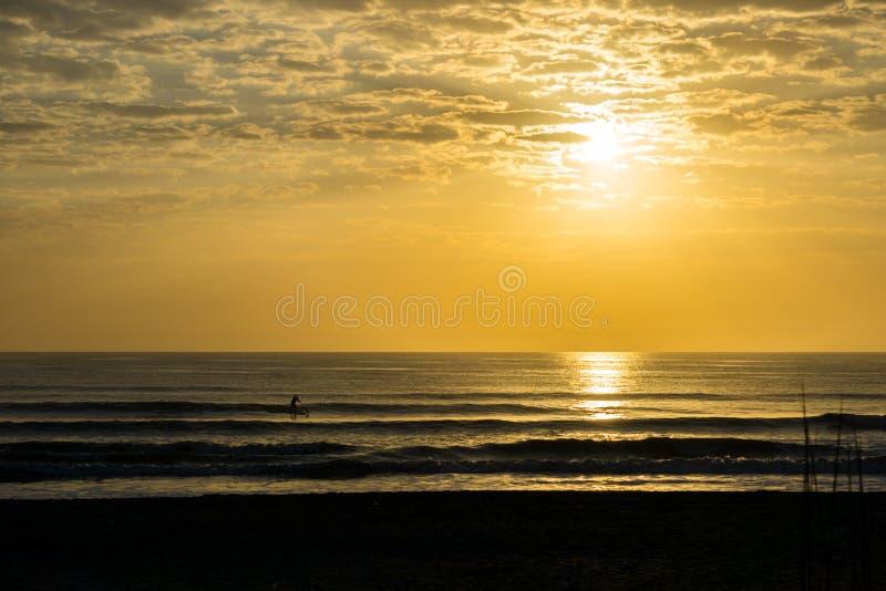 Palette d'homme surfant au lever de soleil images stock