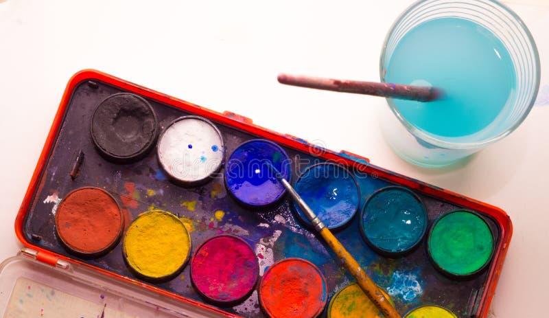 Palette de peinture d'aquarelle avec le verre de l'eau de peinture à côté de lui photographie stock