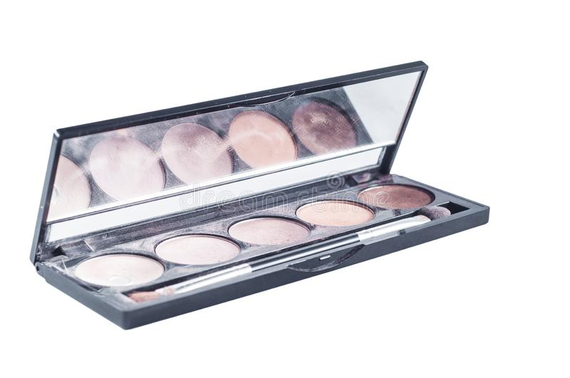 Palette with different shades of face shadows and brush applicator for application. Makeup set with a mirror on a white background. Isolate stock images