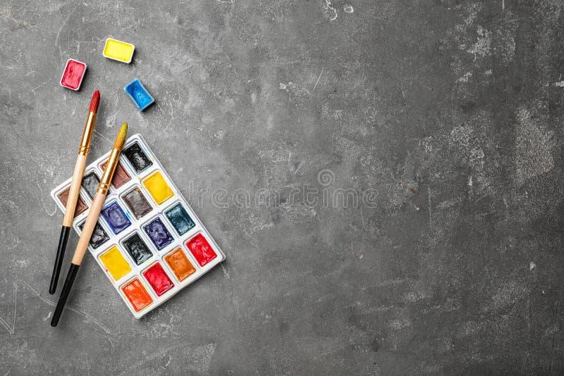 Palette en plastique avec les peintures et les brosses colorées illustration stock