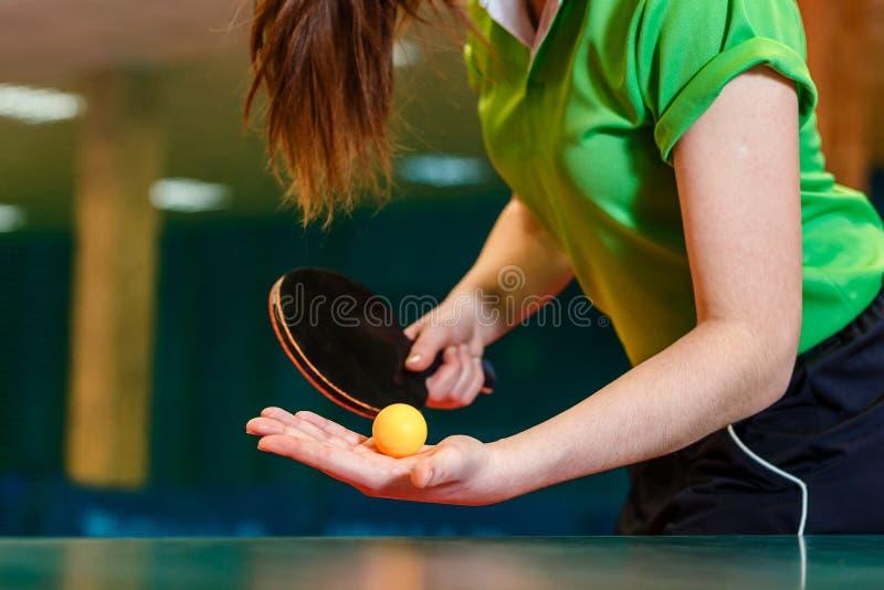 palette et boule de ping-pong dans des mains femelles étroitement Servez la boule dans le ping-pong photographie stock libre de droits