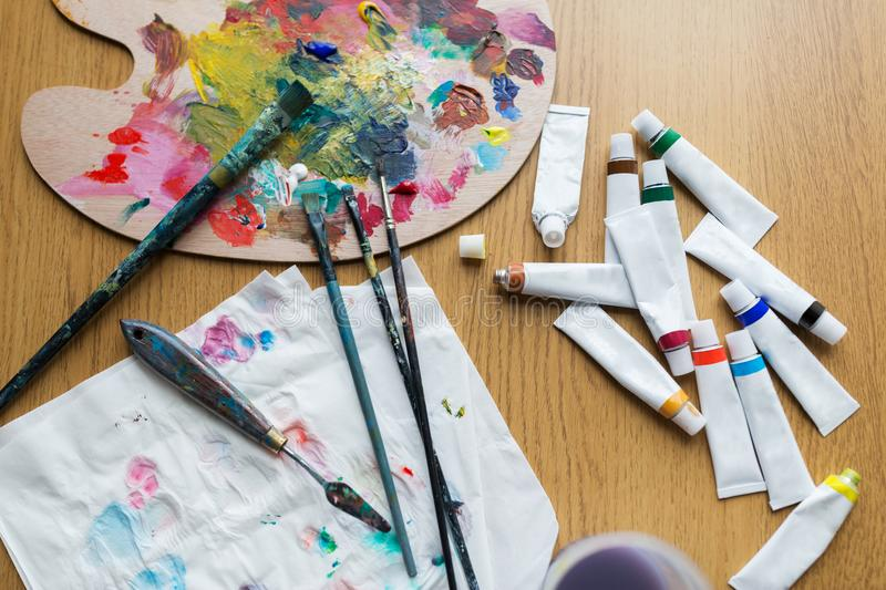 Palette knife, brushes and paint tubes on table. Fine art, creativity and artistic tools concept - palette knife, brushes and paint tubes on table royalty free stock image